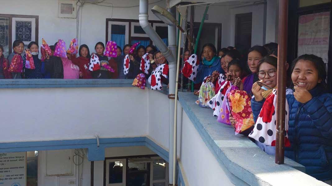 nepal-girls-with-kits-balcony-1068x598